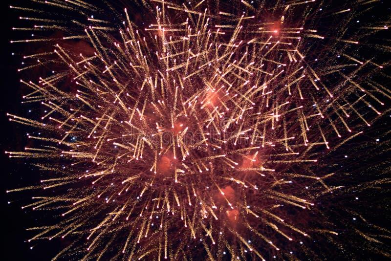 Fogos de artifício efervescentes bonitos baratos, cor vermelho-amarela, com embaçamento, no céu noturno, textura do fundo imagem de stock