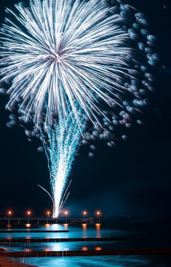 Fogos de artifício finos em um cais do mar, com reflexão no mar e na cidade foto de stock