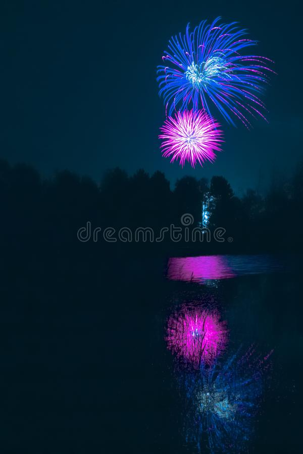 Fogos-de-artifício que explodem sobre a lagoa da floresta fotografia de stock