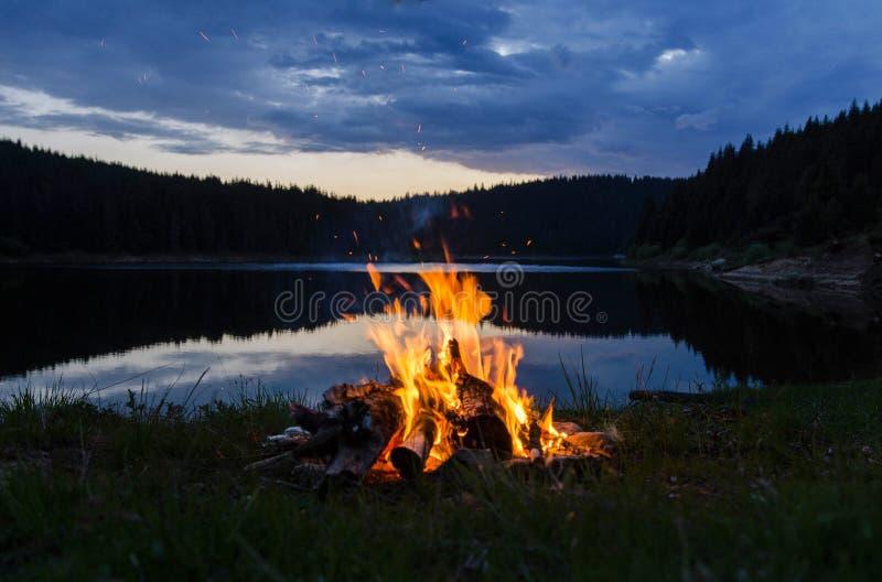 Fogueira após o por do sol nas montanhas ao lado de um lago imagens de stock royalty free