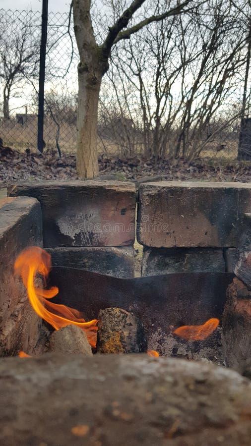 Fogueira com as chamas alaranjadas na chaminé velha feita dos tijolos queimados Fogo do ardor no fundo rústico com ramos de árvor foto de stock
