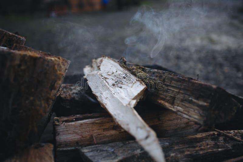 Fogueira na grade A lenha puncionada encontra-se em um fogo em um soldador forjado metal O fogo e o fumo são visíveis fotos de stock royalty free