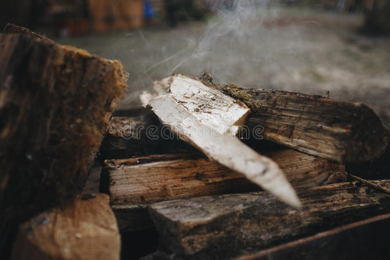 Fogueira na grade A lenha puncionada encontra-se em um fogo em um soldador forjado metal O fogo e o fumo são visíveis foto de stock royalty free