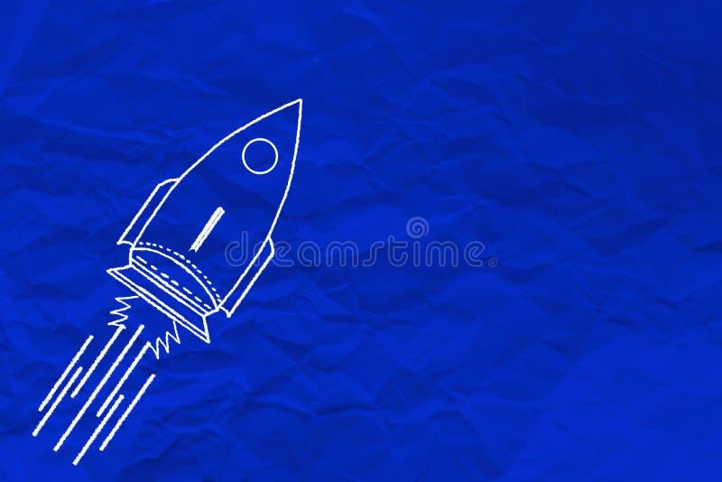Foguete da escrita da mão no papel amarrotado azul fotos de stock royalty free