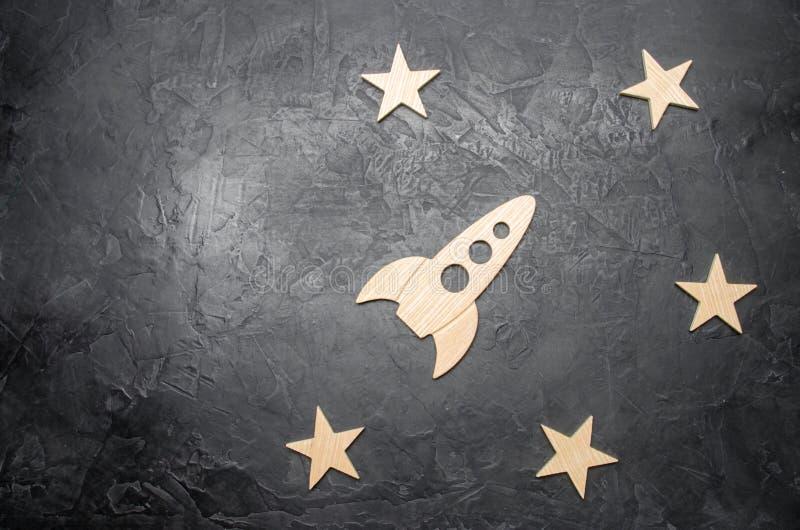 Foguete e estrelas de madeira de espaço em um fundo escuro O conceito das viagens espaciais, o estudo dos planetas e estrelas Edu imagens de stock royalty free