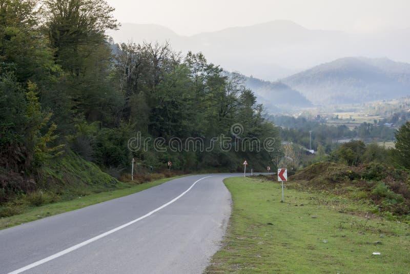 Fogy πρωινού τοπίο με το δρόμο μέσω των χλοωδών λόφων στοκ εικόνες
