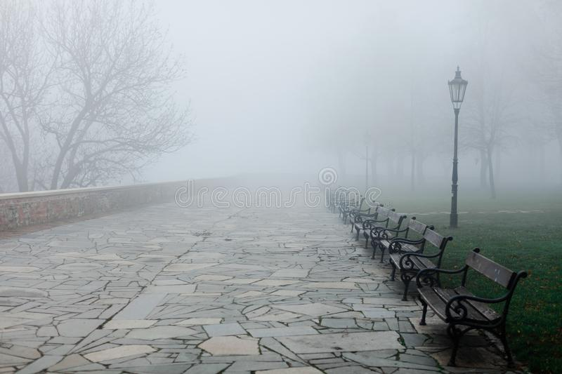 Fogy morning in park, benches disappear in low visibility. Vintage street light in right side royalty free stock photo