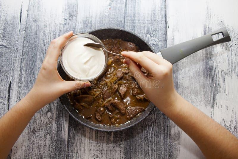 Foie de porc dans la casserole Oignons frits, spatule pour la cuisine image stock