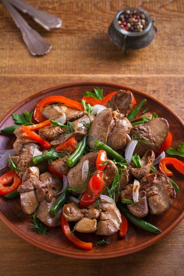 Foie de poulet avec le paprika rouge, les haricots verts et l'oignon Foie sauté avec des légumes d'un plat photo stock