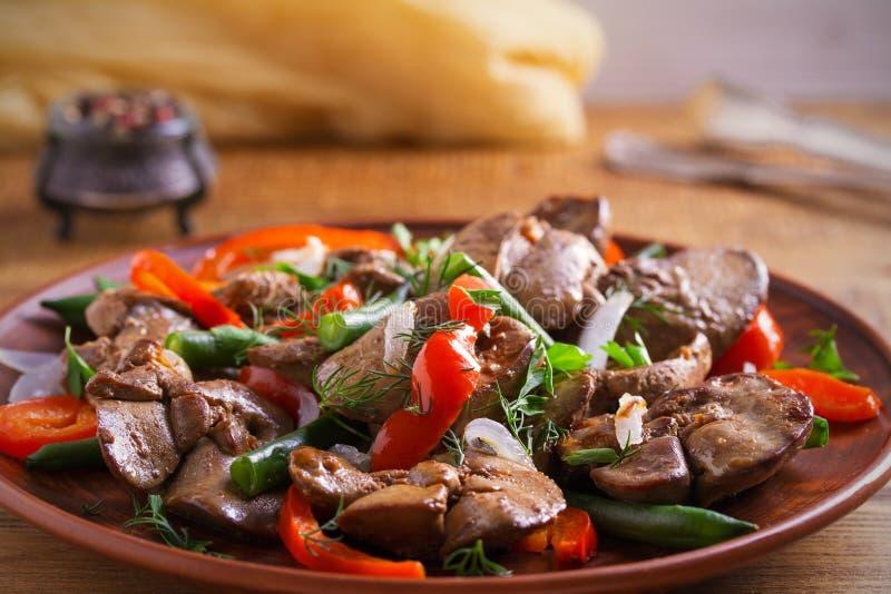 Foie de poulet avec le paprika rouge, les haricots verts et l'oignon Foie sauté avec des légumes d'un plat image stock