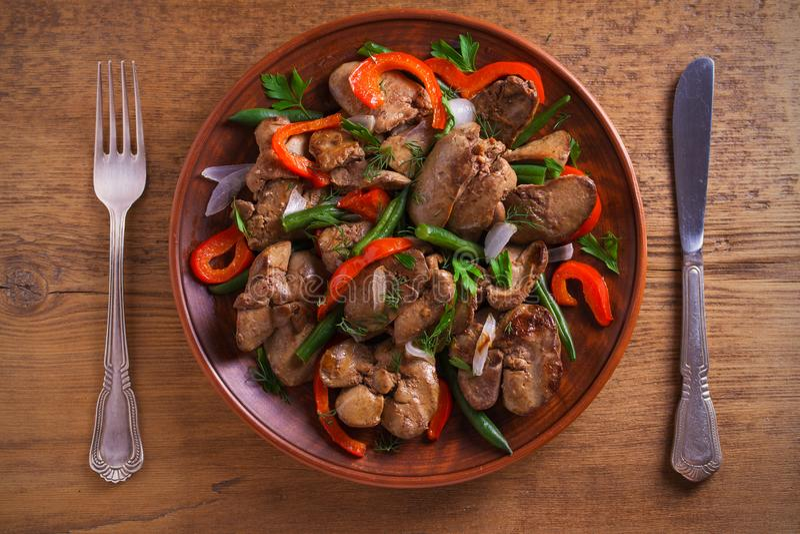 Foie de poulet avec le paprika rouge, les haricots verts et l'oignon Foie sauté avec des légumes d'un plat images stock