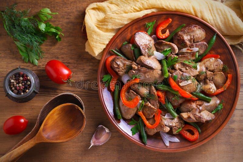 Foie de poulet avec le paprika rouge, les haricots verts et l'oignon Foie sauté avec des légumes d'un plat photographie stock libre de droits
