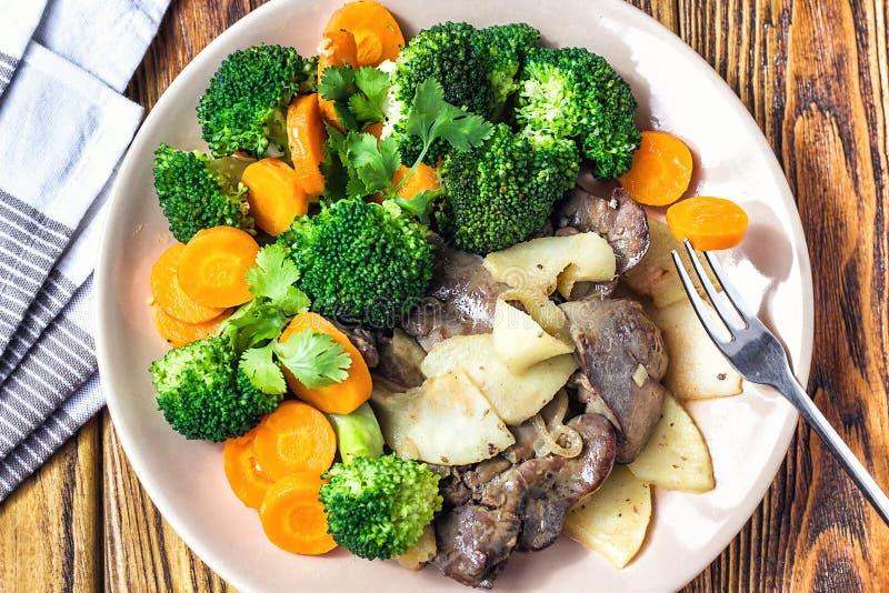 Foie de poulet frit aux oignons et aux herbes de carottes de brocoli de pommes de légumes sur un plat sur la table en bois, vue h image stock