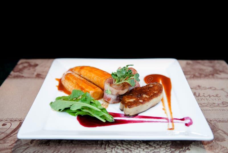 Foie Gras med bacontranbärsås och den caramelized bananen arkivbild