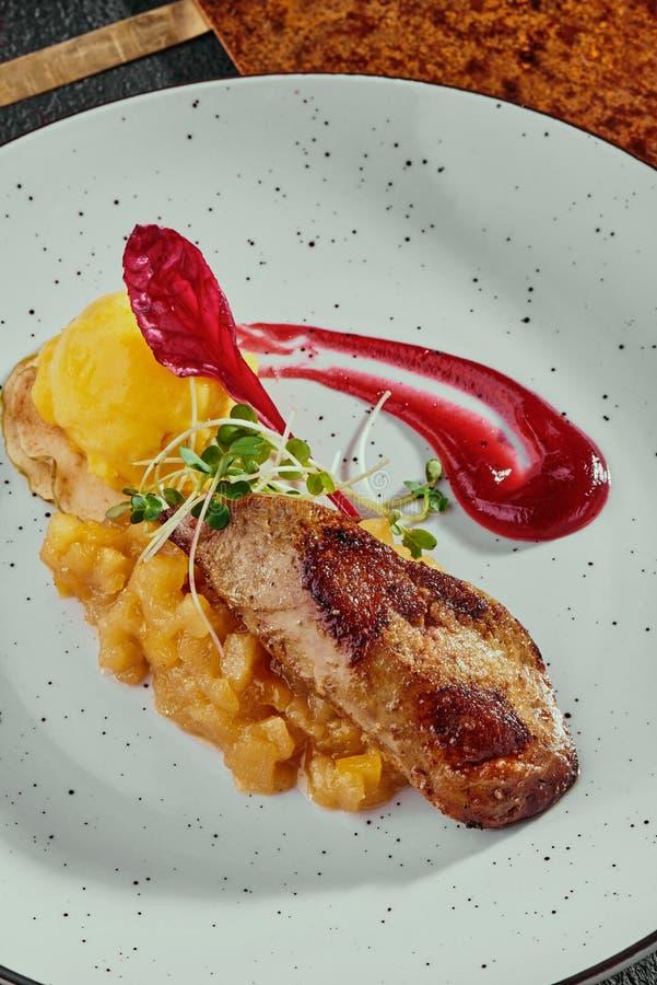 Foie gras med den citrusa chutney- och mangosorbet på en vit platta på en kopparbakgrund fotografering för bildbyråer