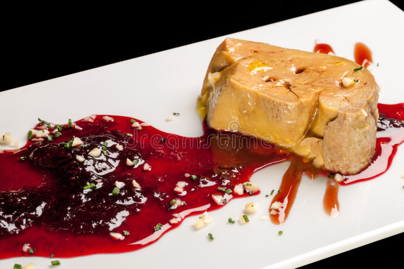 Foie gras with red fruit sauce. stock photos