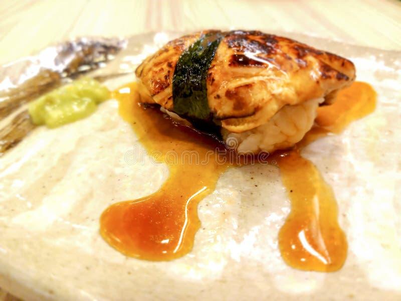 Foie grassushi som slås in i alger och special sås royaltyfri fotografi