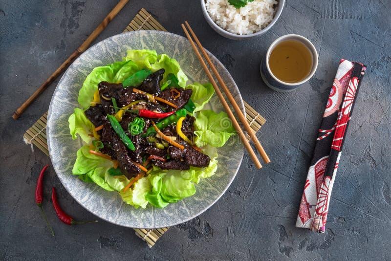 Foie sauté d'Asiatique avec le paprika, les carottes et l'oignon Avec les verts et le riz photos stock
