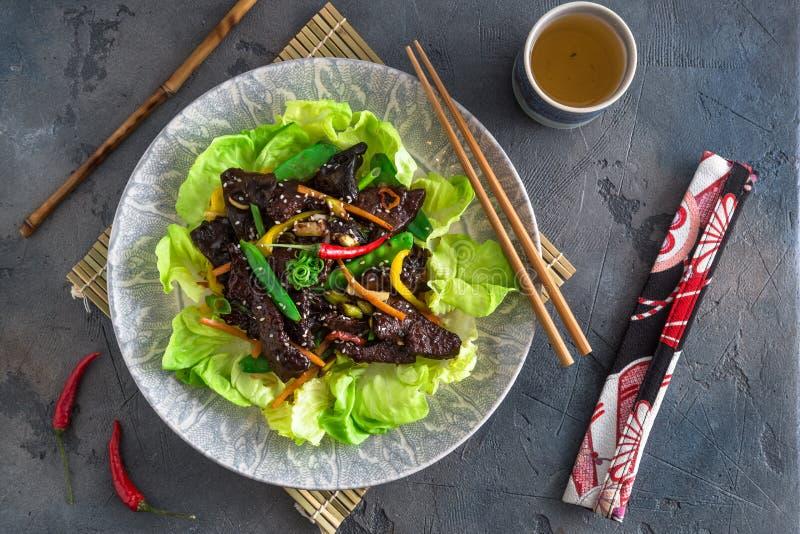 Foie sauté d'Asiatique avec le paprika, les carottes et l'oignon Avec les verts et le riz images libres de droits