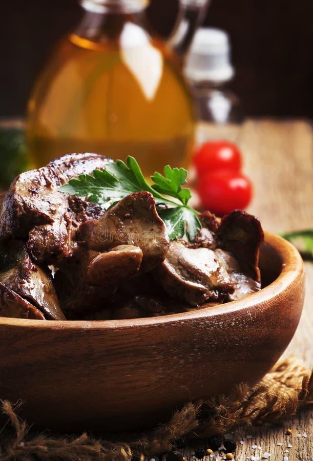 Foies de poulet frit dans la cuvette en bois, fond en bois de table de cuisine de cru, image verticale, foyer sélectif photos libres de droits