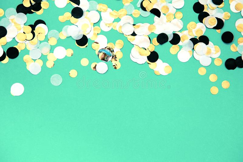 Foil confetti sparse on trendy mint colored background. Gold, silver, black and white foil confetti sparse on trendy mint colored background. Simple holiday royalty free stock image