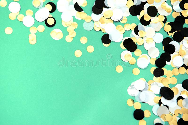 Foil confetti sparse on trendy mint colored background. Gold, silver, black and white foil confetti sparse on trendy mint colored background. Simple holiday royalty free stock photography