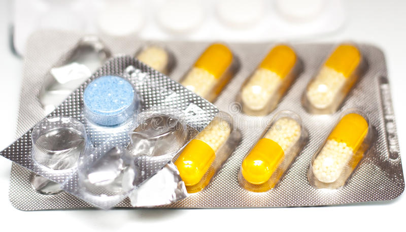 Foil whapped coloured pills. Pharmaceutical medicine blue tablet and yellow with white pills in aliminum foil strip silver foil blister on white background stock photography
