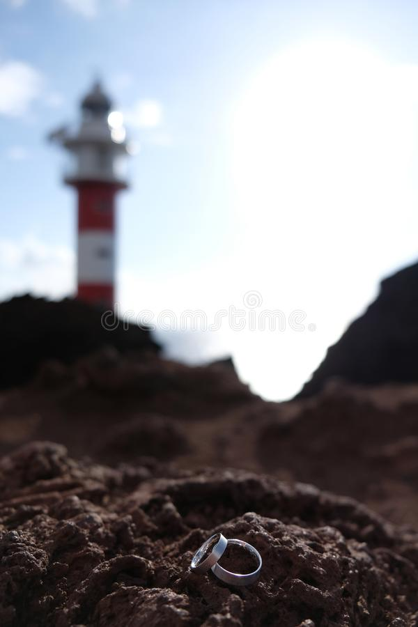 Fokus auf Eheringen auf vulkanischem Felsen mit unscharfem rotem und weißem Leuchtturm auf dem Hintergrund lizenzfreie stockbilder