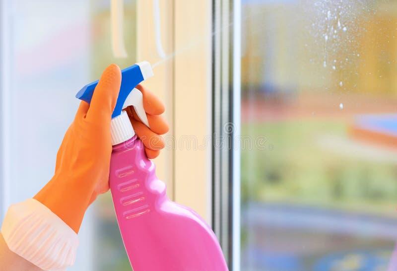Fokus auf Glasoberfläche Spray für das Säubern in Hände stockfoto