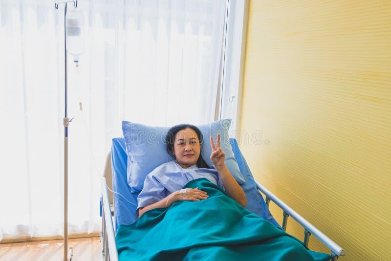 Fokus av den asiatiska medelåldersa kvinnapatienten på sängen för behandling i rumsjukhus arkivfoton
