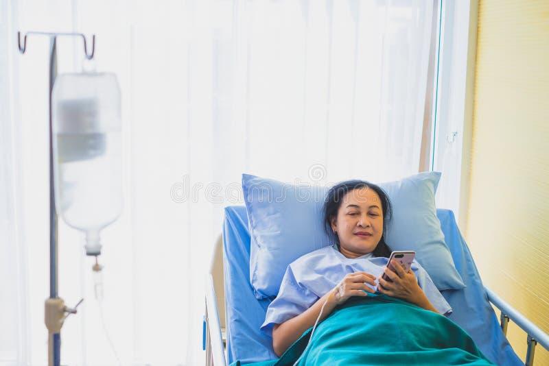 Fokus av den asiatiska medelåldersa kvinnapatienten på sängen genom att använda telefonen, i rumsjukhus fotografering för bildbyråer