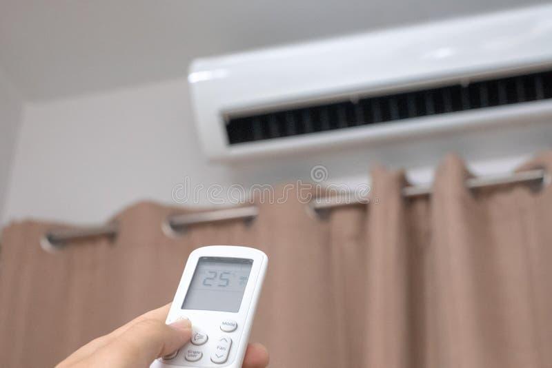 Fokus framåt Luftvillkorkontroll, genom att använda fjärrkontroll och att vända på luftkonditioneringsapparaten på 25 grader arkivbilder