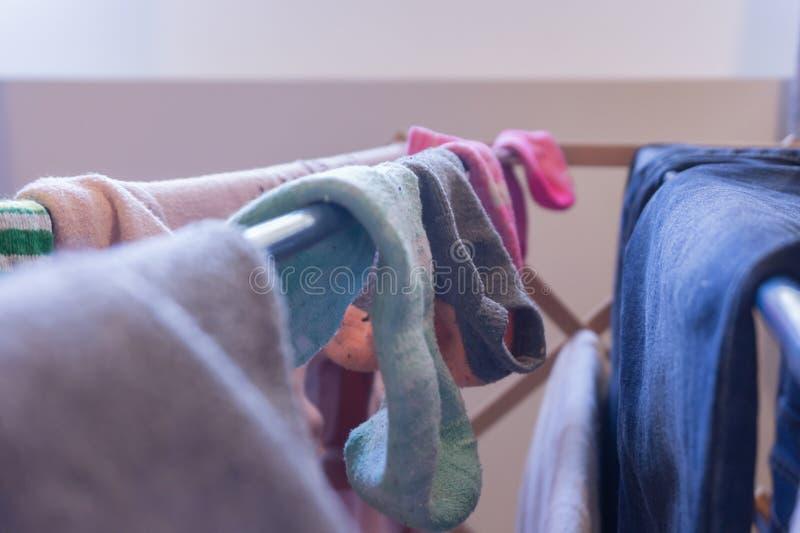 Fokus på ankelsockor som torkar på en tvätterikugge med annan kvinnas kläder, inklusive jeans Matchade dåligt sockor och par av arkivfoton