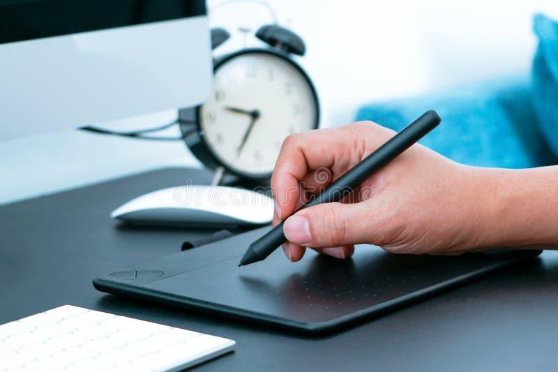 Fokusera på den upptagna grafiska formgivaren som arbetar på datoren vid den digitala pennmusen royaltyfria bilder