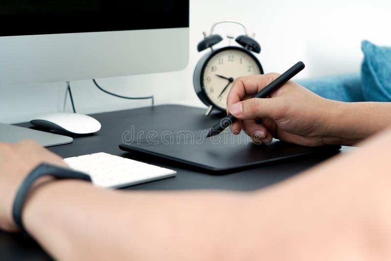 Fokusera på den upptagna grafiska formgivaren som arbetar på datoren vid den digitala pennmusen arkivbilder