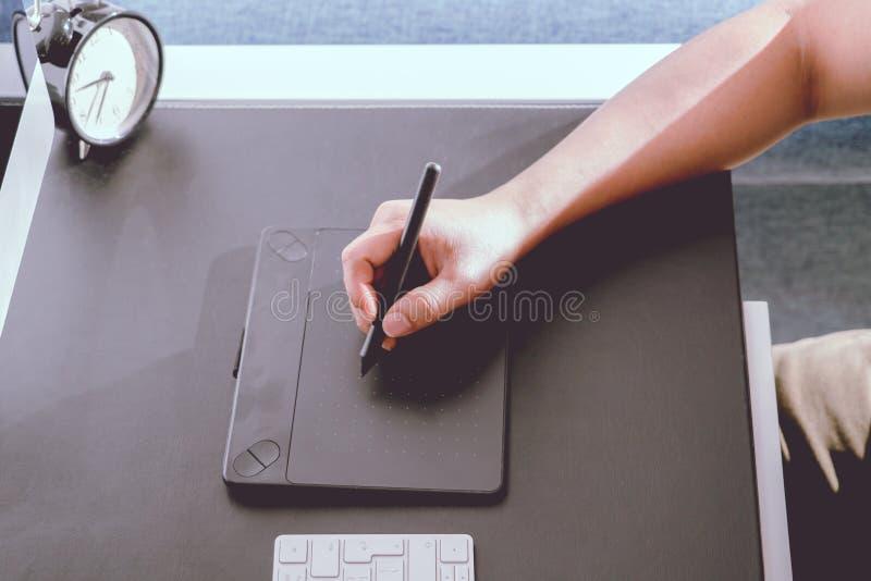 Fokusera på den upptagna grafiska formgivaren som arbetar på datoren vid den digitala pennmusen, oväsenfilter, applicerar royaltyfri fotografi