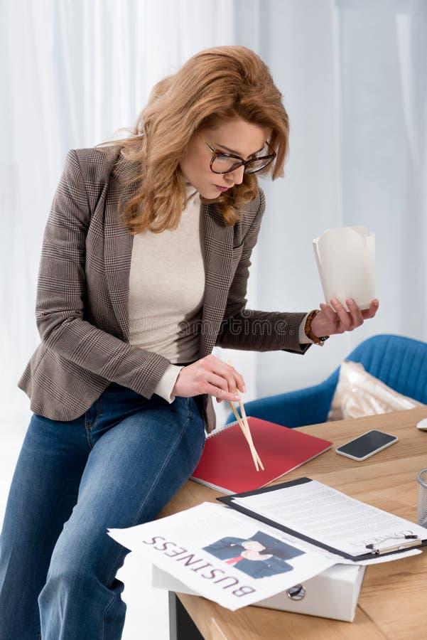 fokuserad affärskvinna med den asiatiska matasken som gör skrivbordsarbete på arbetsplatsen royaltyfri foto