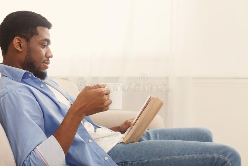 Fokuserad afrikansk amerikanaffärsmanläsebok hemma fotografering för bildbyråer