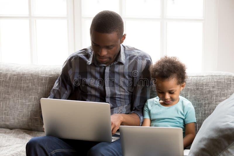 Fokuserad afrikansk amerikanfamilj som tillsammans använder bärbara datorer hemma arkivfoto