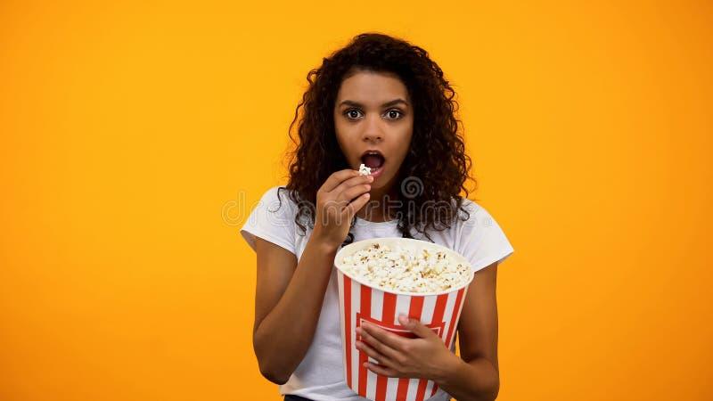 Fokuserad afrikansk amerikankvinna som ?ter popcorn och h?ller ?gonen p? intressera show royaltyfri foto