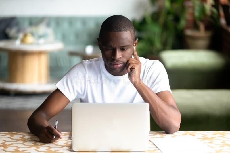 Fokuserad afrikansk amerikanman som använder bärbara datorn i kafé fotografering för bildbyråer