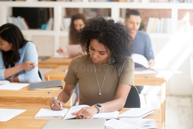 Fokuserad afrikansk kvinnlig högskolahögstadiumstudent som studerar i klassrum arkivbild
