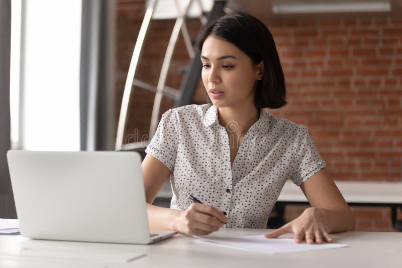 Fokuserad asiatisk affärskvinna som arbetar se bärbara datorn som gör anmärkningar arkivbild