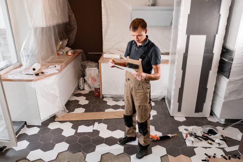 Fokuserad flitig arbetare som kontrollerar rum och planerar reparationsarbete reparation av matsalen i huset, kök royaltyfri fotografi