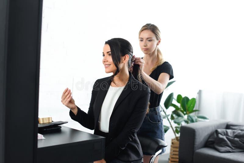 fokuserad frisör som gör frisyren, medan le affärskvinnan arkivfoto