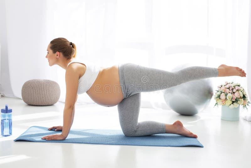 Fokuserad gravid kvinna som ut finner före födseln yoga royaltyfria foton
