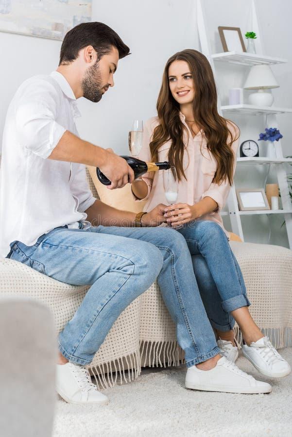 fokuserad hällande champagne för ung man in i exponeringsglas, medan sitta på soffan med att le flickvännen arkivbilder