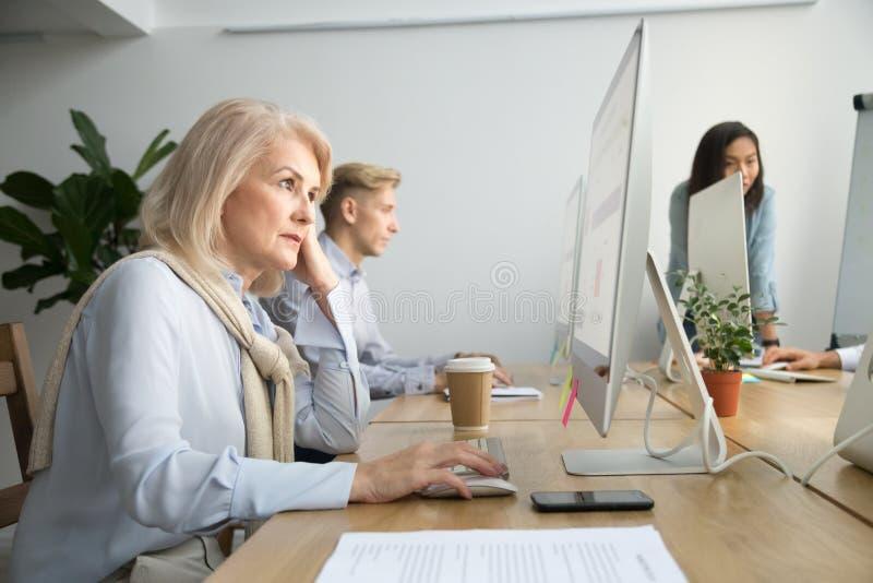 Fokuserad hög affärskvinna som arbetar på skrivbords- sammanträde på offic arkivfoton