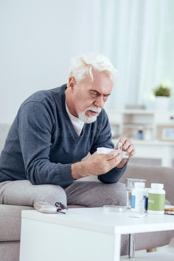 Fokuserad hög man som räknar preventivpillerar arkivbilder