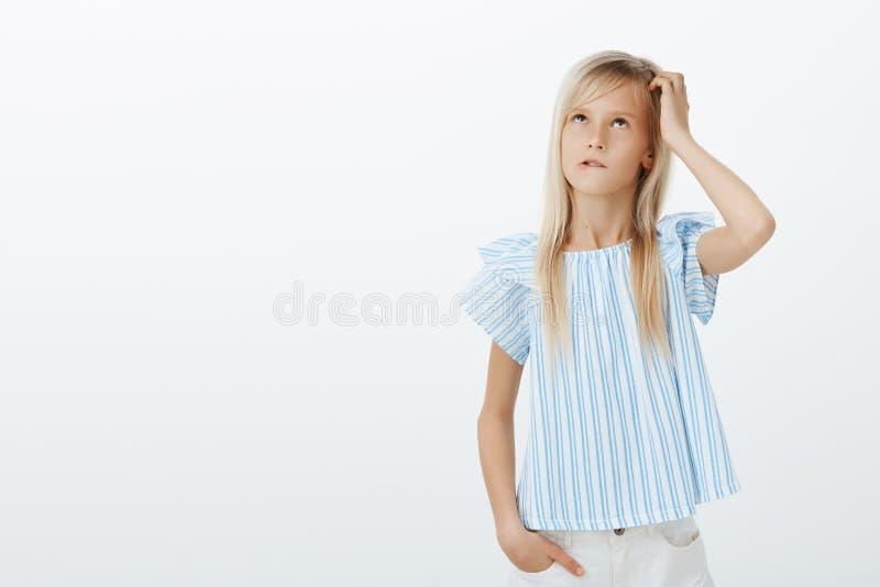 Fokuserad korkad flicka som försöker att beräkna i åtanke nära svart tavla Stående av den förvirrade ifrågasatte ungen i stilfull royaltyfria foton